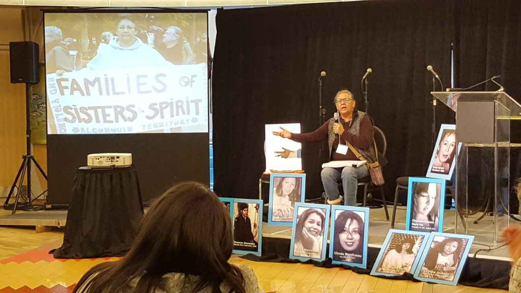 Bridget sits among posters of missing and murdered indigenous women.